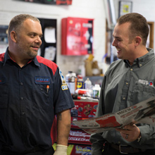 Mobile franchise owner speaking with an automotive technician in a middle of a shop.